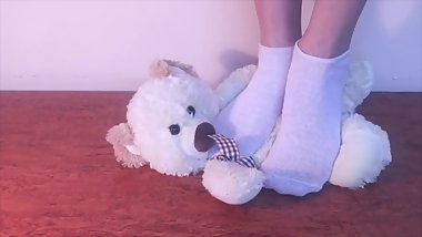 Hot teen girl crush a naughty teddy bear with her sexy foot in socks
